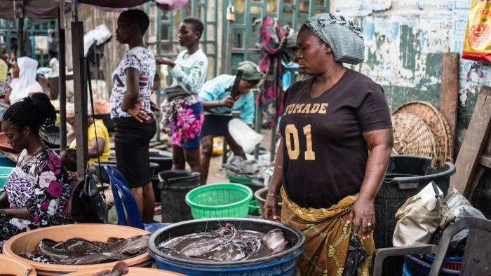 In community of Isale Ijebu in Ajah, Lagos; Tinu mans the front of her market stand where she sells catfish surrounded by other vendors
