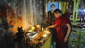 A monk taking part in morning prayers at Thiksey monastery