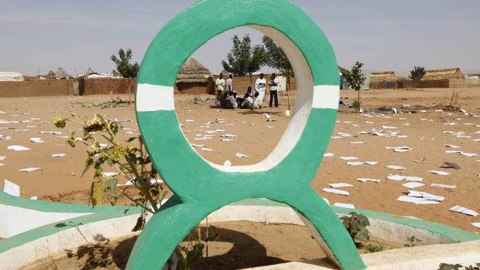 Sudanese refugees are seen through the Oxfam logo at the site of the looted compound of the expelled British aid group, Oxfam at Al Salam refugee camp, outside the Darfur town of al-Fasher, Sudan Saturday, March 21, 2009. Al Salam refugee camp leaders in Darfur say a dozen men broke into the warehouse of an expelled British aid group, Oxfam, stealing all its contents. (AP Photo/Nasser Nasser)
