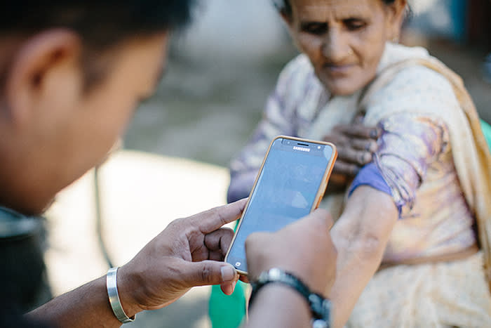 A woman in Nepal has her skin lesions scanned for leprosy using a smartphone