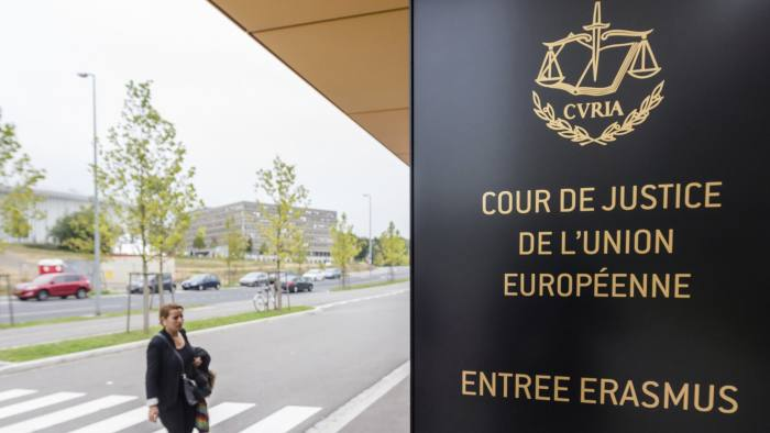 File - In this Oct. 5, 2015 file photo, a woman walks by the entrance to the European Court of Justice in Luxembourg. The European Union's highest court is hearing arguments Tuesday, Nov. 27, 2018 on whether Britain could unilaterally revoke its decision to leave the EU ahead of its planned exit date of March 29, 2019. (Geert Vanden Wijngaert, File)