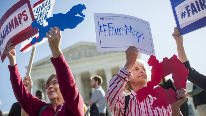 UNITED STATES - OCTOBER 03: Shirley Connuck, right, of Falls Church, Va., holds up a sign representing a district in Texas, as the Supreme Court hears a case on possible partisan gerrymandering by state legislatures on October 3, 2017. (Photo By Tom Williams/CQ Roll Call)
