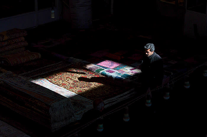 The shadow of a man falls on a Persian carpet layed out in the rug bazaar in Tehran, Iran, on Monday, Jan. 15, 2018. The U.S. presidentplans on stickingwith an agreement that suspends American sanctions on Iran in return for limiting its nuclear research, according to two administration officials familiar with the matter. Photographer: Ali Mohammedi/Bloomberg