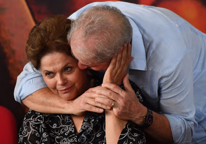 TOPSHOT - Former Brazilian president Luiz Inacio Lula da Silva (R) whispers to former Brazilian president Dilma Rousseff, during a campaign rally to launch Lula's presidential candidacy for the upcoming October elections, at the Workers Central Union (CUT) headquarters in Sao Paulo, Brazil on January 25, 2018. A Brazilian appeals court Wednesday upheld ex-president Luiz Inacio Lula da Silva's conviction for corruption, dealing a body blow to his hopes of running for re-election this year. The three-judge panel sitting in the southern city of Porto Alegre unanimously ruled that his original 9.5-year jail sentence be extended to more than 12 years. Lula was defiant, telling he intends to run for the presidency despite the court setback.  / AFP PHOTO / Nelson AlmeidaNELSON ALMEIDA/AFP/Getty Images