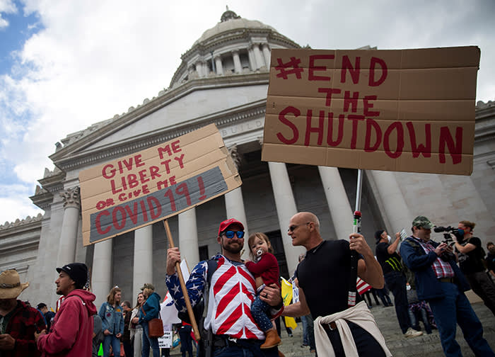 Demonstrators gather in Olympia, Washington to protest against the state's stay-at-home orders. Trump adviser Stephen Moore says he told the president 'this lockdown is causing more deaths and misery than the disease itself'
