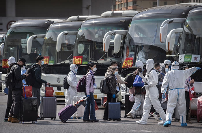 BEIJING, CHINA - APRIL 08: Chinese workers and health officials wear protective white suits as travellers from Wuhan gather to take buses as they are processed and taken to do 14 days of quarantine, after arriving on the first trains to Beijing on April 8, 2020 in Beijing, China. China lifted its lockdown on Wuhan, the first epicentre of COVID-19 after 76 days, allowing healthy people to leave. China recorded for the first time since January 21st no coronavirus-related deaths. With the pandemic hitting hard across the world, officially the number of coronavirus cases in China is dwindling, ever since the government imposed sweeping measures to keep the disease from spreading. For more than two months, millions of people across China have been restricted in how they move from their homes, while other cities have been locked down in ways that appeared severe at the time but are now being replicated in other countries trying to contain the virus. Officials believe the worst appears to be over in China, though there are concerns of another wave of infections as the government attempts to reboot the worlds second largest economy. In Beijing, it is mandatory to wear masks outdoors, some retail stores still operate on reduced hours, restaurants employ social distancing among patrons, and tourist attractions at risk of drawing large crowds remain closed or allow only limited access. Monitoring and enforcement of virus-related measures and the quarantine of anyone arriving to Beijing is carried out by neighborhood committees and a network of Communist Party volunteers who wear red arm bands. Since January, China has recorded more than 81,000 cases of COVID-19 and at least 3200 deaths, mostly in and around the city of Wuhan, in central Hubei province, where the outbreak first started. (Photo by Kevin Frayer/Getty Images)
