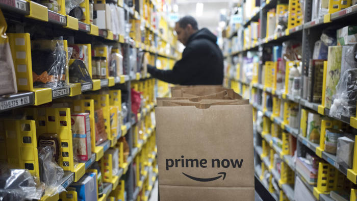 FILE - In this Dec. 20, 2017, file photo, a clerk reaches to a shelf to pick an item for a customer order at the Amazon Prime warehouse in New York. Amazon's Prime Day starts July 16, 2018, and will be six hours longer than last year's and will launch new products. Amazon hopes to keep Prime attractive for current and would-be subscribers after raising the annual membership fee by 20 percent to $119 and to $12.99 for the month-to-month option.. (AP Photo/Mark Lennihan, File)