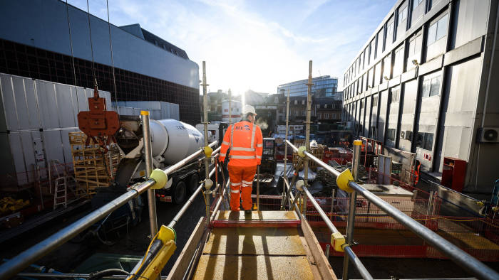 LONDON, ENGLAND - DECEMBER 19: A construction worker walks through part of the site at the Farringdon Crossrail station, on December 19, 2017 in London, England. Transport for London has announced today that the Elizabeth Line will open in December 2018, with three sections operating services. The new high-speed line will include ten new stations. (Photo by Leon Neal/Getty Images)