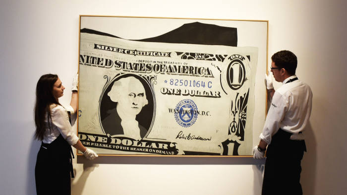 LONDON, ENGLAND - JUNE 08: Two gallery assistants pose wih 'Silver Certificate, 1962' by Andy Warhol which has an estimated value of £13-18 million and is going on show at Sotheby's on June 8, 2015 in London, England. The work is a centrepiece of an exhibition of 21 works inspired by the US Dollar which are estimated to have a total value of £50 million and will go under offer by the auction house on 1st and 2nd July 2015. (Photo by Mary Turner/Getty Images)