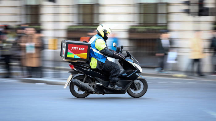 A food delivery courier, working for Just Eat Plc, travels in London, U.K., on Thursday, Dec. 22, 2016. The food delivery business model has proven attractive to venture capitalists, who last year poured $5.5 billion into food-delivery companies globally, according to research firm CB Insights. Photographer: Simon Dawson/Bloomberg