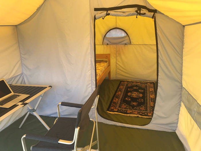 A climber's tent at the 7 Summits Club base camp, complete with wooden bed and separate office area