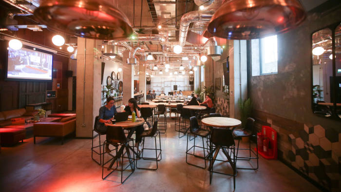 Residents work in one of the communal spaces at the co-living building The Collective Old Oak in north west London on October 11, 2017. The 10-storey building may look like a hotel, but it is actually a large-scale house-share -- the biggest of its kind, according to its developers -- offering modest rooms and upscale services for hundreds of young adults caught in London's housing crisis. / AFP PHOTO / Daniel LEAL-OLIVAS / TO GO WITH AP STORY BY MARTINE PAUWELS (Photo credit should read DANIEL LEAL-OLIVAS/AFP/Getty Images)
