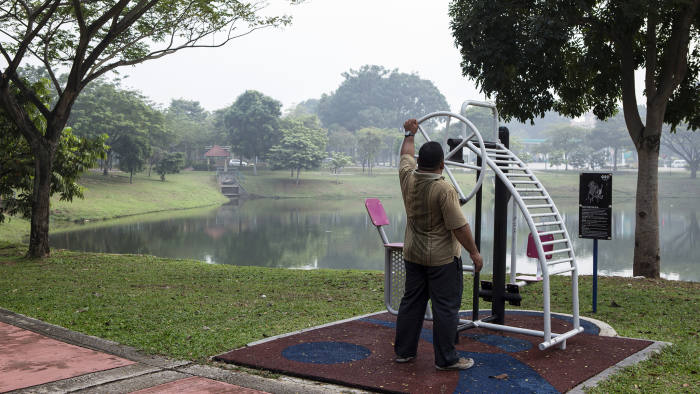 A man exercises at a park along Putrajaya Lake in Putrajaya, Malaysia, on Thursday, Oct. 1, 2015. Malaysia may miss a goal to balance its budget by 2020 as a plunge in commodity prices forces the government to cut its projections, according to Prime Minister Najib Razak. Photographer: Charles Pertwee/Bloomberg