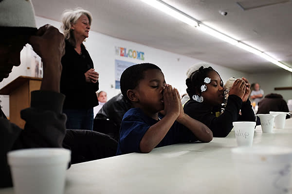 A family prays before a meal at the Seashore Mission which offers services to the homeless and those in need on January 3, 2016 in Biloxi, Mississippi