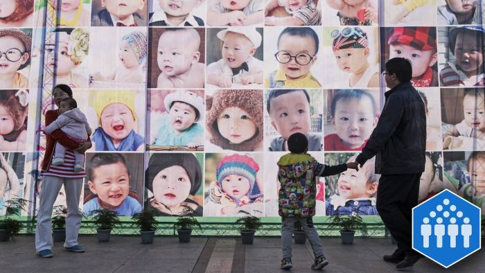 TAIZHOU, CHINA - NOVEMBER 17: (CHINA OUT) People pass a poster printed with babaies' faces on November 17, 2013 in Taizhou, Zhejiang Province of China. China has decided to abandon its 35-year-old one-child policy, allowing all couples to have two children, the Communist Party of China (CPC) announced after a key meeting on Thursday.  (Photo by VCG/VCG via Getty Images)