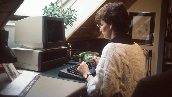DC96YD A young woman in front of her computer in home office, photographed in 1986.