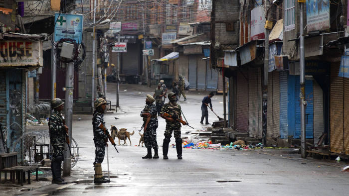 FILE- In this Aug. 8, 2019, file photo, Indian paramilitary soldiers stand guard on a deserted street during curfew in Srinagar, Indian controlled Kashmir. The beautiful Himalayan valley is flooded with soldiers and roadblocks of razor wire. Phone lines are cut, internet connections switched off, politicians arrested. Narendra Modi, the prime minister of the world's largest democracy has clamped down on Kashmir to near-totalitarian levels. (AP Photo/Dar Yasin, file)