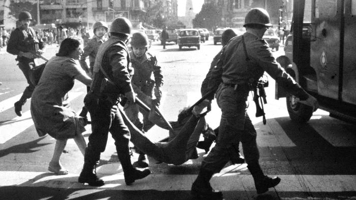 """A woman tries desperately to prevent detention of a young man by police during anti-government rally in Buenos Aires during the last days of Argentina's Dirty War. A 1976 coup resulted in a 7-year military dictatorship in which an estimated 30,000 people were killed or """"disappeared"""" at the hands of the military. (Photo by Horacio Villalobos/Corbis via Getty Images)"""