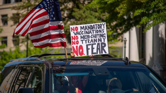 """A woman holds a sign voicing various conspiracy theories believed by QAnon followers out of the sunroof of a car at the """"Reopen Virginia"""" protest in Richmond on April 22nd, 2020. Three Percenters are a movement that advocates for constitutional rights, and takes its name from the belief that only three percent of America took up arms against the British during the Revolutionary War. (Photo by Matthew Rodier/Sipa USA)"""