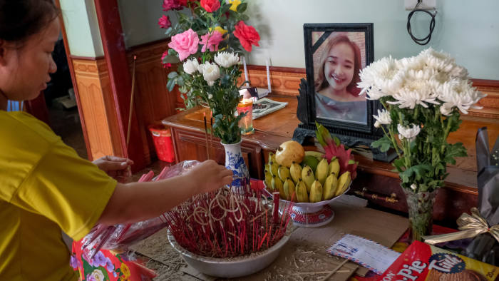 NGHE AN, VIETNAM - OCTOBER 28: Bui Thi Phuong, 25, lights incense at a makeshift shrine with the photo of her younger sister Bui Thi Nhung, believed to be one of the 39 victims found dead in a refrigerated truck in Britain, at their house on October 28, 2019 in Nghe An province, Vietnam. A lorry was discovered early Wednesday morning in Waterglade Industrial Park on Eastern Avenue in the town of Grays. Authorities said they believed the lorry originated in Bulgaria and entered the country at Holyhead on October 19. The suspected driver was arrested in connection with the investigation. (Photo by Linh Pham/Getty Images)