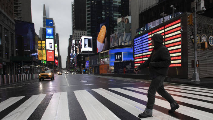 A man crosses the street in a nearly empty Times Square, which is usually very crowded on a weekday morning, Monday, March 23, 2020 in New York. Gov. Andrew Cuomo has ordered most New Yorkers to stay home from work to slow the coronavirus pandemic. (AP Photo/Mark Lennihan)