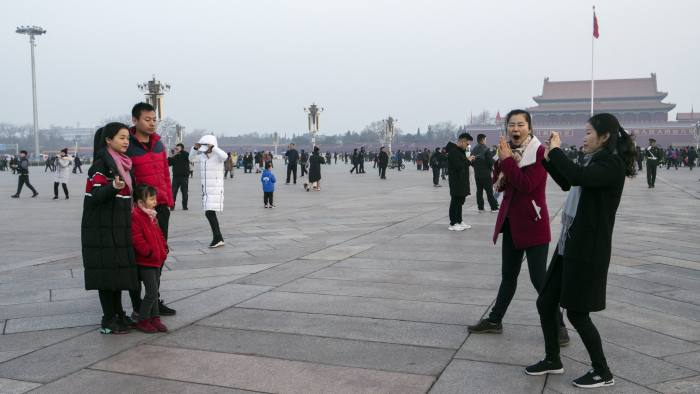 A family poses for photographs at Tiananmen Square in Beijing, China, on Monday, March 4, 2019. National People's Congress spokesman Zhang Yesui said at a briefing on Monday that China would need to increase its military spending to protect itself and that it doesn't pose a threat to other countries. Photographer: Giulia Marchi/Bloomberg