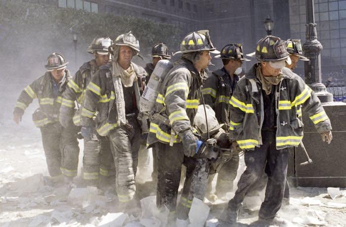 NUEVA YORK, NUEVA YORK - 11 DE SEPTIEMBRE DE 2001: los bomberos del FDNY llevan a otro bombero, Al Fuentes, que resultó herido en el colapso del World Trade Center el 11 de septiembre de 2001. (Foto de Matt Moyer / Corbis a través de Getty Images)