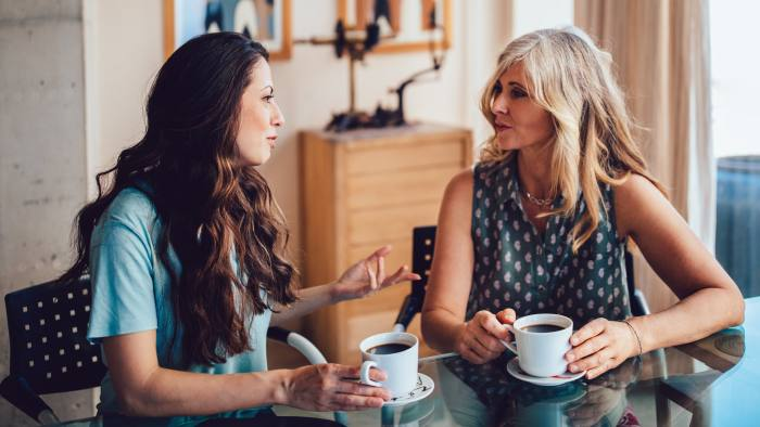 Older mother and daughter spending time together at home drinking coffee and discussing