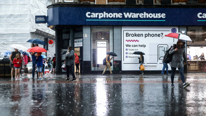 Pedestrians use umbrellas to shelter from the rain as they pass a Carphone Warehouse retail store, operated by DixonsCarphonePlc, in central London, U.K., on Tuesday, May 29, 2018. DixonsCarphonePlcshares plunged the most in nine months after the retailer forecast that earnings this year will slump about 21 percent as it closes mobile-phone stores in a contracting U.K. household-electronics market. Photographer: Simon Dawson/Bloomberg