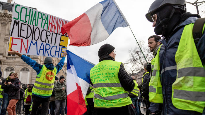 Demonstrators wearing yellow vests (Gilets jaunes) wave French national flags during protests on the Champs-Elysees in Paris, France on Saturday, Jan. 26, 2019. French President Emmanuel Macron plans changes in the staff at the Elysee Palace following months of protests from the Yellow Vests movement, Le Parisien reported, citing government officials it didn't name. Photographer: Anita Pouchard Serra/Bloomberg