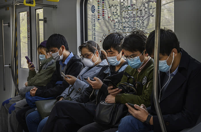 BEIJING, CHINA - APRIL 15: Chinese commuters wear protective masks as they look at their mobile phones while riding the subway during rush hour on April 15, 2020 in Beijing, China. China lifted its lockdown on Wuhan, the first epicentre of COVID-19 after 76 days last week, allowing healthy people to leave. With the pandemic hitting hard across the world, officially the number of coronavirus cases in China is dwindling, ever since the government imposed sweeping measures to keep the disease from spreading. For more than two months, millions of people across China have been restricted in how they move from their homes, while other cities have been locked down in ways that appeared severe at the time but are now being replicated in other countries trying to contain the virus. Officials believe the worst appears to be over in China, though there are concerns of another wave of infections as the government attempts to reboot the worlds second largest economy. Since January, China has recorded more than 81,000 cases of COVID-19 and at least 3200 deaths, mostly in and around the city of Wuhan, in central Hubei province, where the outbreak first started. (Photo by Kevin Frayer/Getty Images)