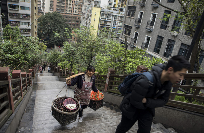 CHONGQING, CHINA - 4 APRIL 2019. A young man and a woman carrying fruit to sell climb stairs in central Chongqing. (Giulia Marchi for The Financial Times)