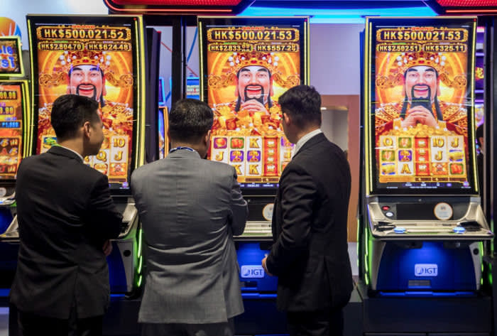 Attendees play electronic slot machines during the Global Gaming Expo Asia (G2E Asia) in Macau, China, on Tuesday, May 21, 2019. The expo runs through May 23. Photographer: Paul Yeung/Bloomberg via Getty Images