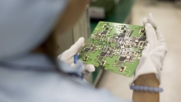 An employee inspects smartphone circuit boards in a manufacturing facility at ZTE Corp.'s headquarters in the Nanshan district of Shenzhen, China, on Thursday, Aug. 7, 2014. ZTE, a Chinese maker of telecommunications equipment and systems, is scheduled to report second quarter earnings on Aug. 20. Photographer: Brent Lewin/Bloomberg