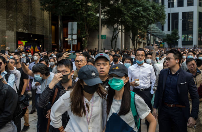 Office workers and demonstrators watch as riot police gather on Pedder Street during a protest in the Central district of Hong Kong, China, on Monday, Nov. 11, 2019. A Hong Kong protester was in critical condition after being shot by a police officer, as the financial hub reeled from citywide efforts to disrupt the work week amid worsening political unrest. Photographer: Nicole Tung/Bloomberg