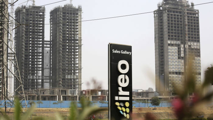 A signboard advertising IREO stands in front of buildings being constructed by the real estate firm in Gurgaon, India, Tuesday, March 20, 2018. The Indian company that is partnering with the Trump Organization on an office tower project has been accused of running an elaborate real estate swindle that cheated investors out of nearly $150 million, according to complaints filed with Indian authorities. The documents make no mention of the Trump Organization, and focus largely on two real estate deals that began years before the organization signed a 2016 agreement with IREO to partner on an office tower in Gurgaon, outside New Delhi. (AP Photo/Oinam Anand)