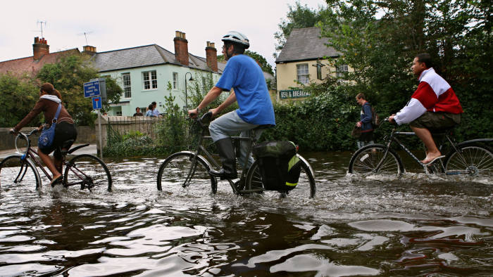 OXFORD, UNITED KINGDOM - JULY 25: Residents make their way through the flood waters as they leave their flooded neighbourhood on July 25, 2007 near Otney Island in West Oxford, England. Flood levels in the Thames are expected to peak today, with numerous properties already flooded. (Photo by David Silverman/Getty Images)