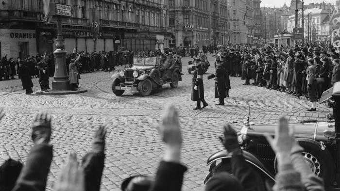 Austrian citizens give the Nazi salute as German Wehrmacht troops and artillery parade through the streets of Vienna after the German Fuhrer and Chancellor Adolf Hitler had entered the city proclaiming Anschluss, the term applied to the annexation of Austria into Nazi Germany on 15th March 1938 in Vienna, Austria. (Photo by London Express/Hulton Archive/Getty Images)