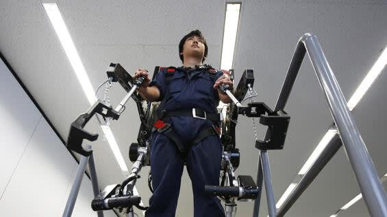 An employee of ActiveLink Co., established under the intrapreneurship of Panasonic Corp, demonstrates the company's PowerLoader light PLL-011E in Tokyo June 2, 2014. The PowerLoader is a robotic exoskeleton that is developed to help farmers and construction workers. It has two other variants, the compact PowerLoader Ninja, that weighs only 15 kg (33 lbs), and a PowerLoader built to lift objects that weigh up to 220 kg (485 lbs). The system functions by measuring the direction, rotation and force of pressure that a user applies, translating that into the movement of the machine. REUTERS/Issei Kato (JAPAN - Tags: SCIENCE TECHNOLOGY SOCIETY BUSINESS) - RTR3RSF1