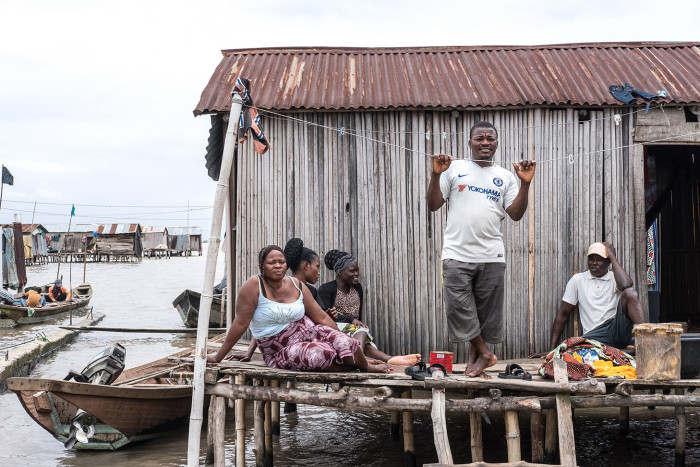 In the informal fishing community of Isale Ijebu in Ajah. Juliet sits outside her home with her family in front of their home of which they've been given an eviction notice.