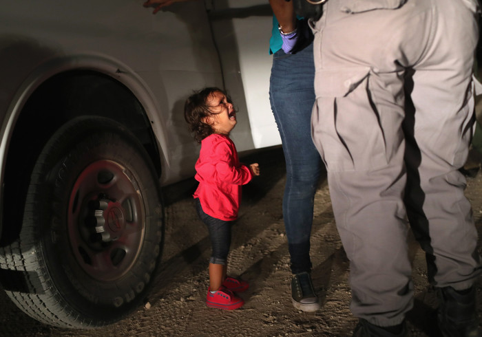 """MCALLEN, TX - JUNE 12: A two-year-old Honduran asylum seeker cries as her mother is searched and detained near the U.S.-Mexico border on June 12, 2018 in McAllen, Texas. The asylum seekers had rafted across the Rio Grande from Mexico and were detained by U.S. Border Patrol agents before being sent to a processing center for possible separation. Customs and Border Protection (CBP) is executing the Trump administration's """"zero tolerance"""" policy towards undocumented immigrants. U.S. Attorney General Jeff Sessions also said that domestic and gang violence in immigrants' country of origin would no longer qualify them for political asylum status. (Photo by John Moore/Getty Images)"""