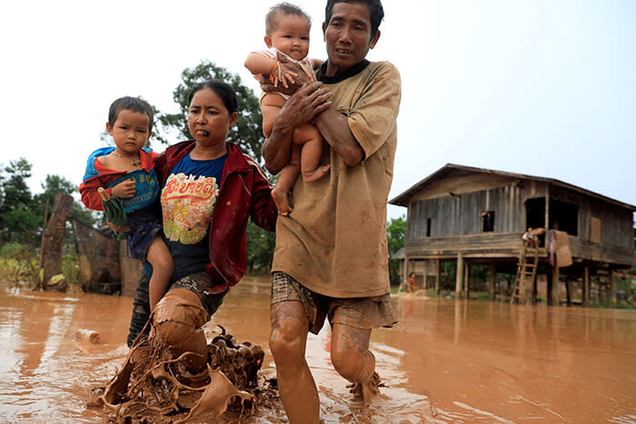 Parents carry their children as they leave their home during the flood after the Xepian-Xe Nam Noy hydropower dam collapsed in Attapeu province, Laos July 26, 2018. REUTERS/Soe Zeya Tun TPX IMAGES OF THE DAY