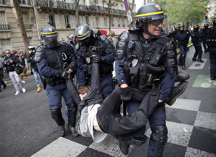 Riot police officers detain a demonstrator during a demonstration in Paris, Tuesday, May 22, 2018. French public services workers have gone on strike as part of their protest a government plan to cut 120,000 jobs by 2022. (AP Photo/Christophe Ena)