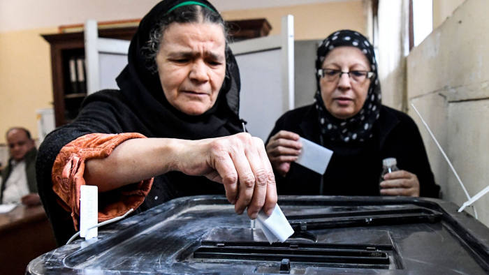 TOPSHOT - Elderly Egyptian women cast their ballots in a box as they vote at a polling station in a referendum on constitutional amendments, at a school in the capital Cairo's northern neighbourhood of Shubra, on the first day of a three-day poll, on April 20, 2019. - Polls in Egypt opened on April 20 for 62 million eligible voters to make their voice hear on a referendum that could keep President Abdel Fattah al-Sisi in power until 2030. On the ballot is a raft of constitutional changes that would extend Sisis current term by two years. He would be eligible to run for six more years in 2024. (Photo by Khaled DESOUKI / AFP)KHALED DESOUKI/AFP/Getty Images