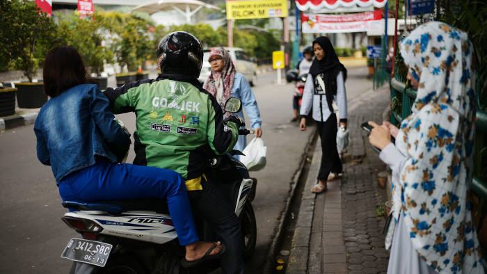 A Go-Jek motorcycle driver drops off a passenger in Jakarta, Indonesia, on Sunday, Aug. 13, 2017. President Joko Widodo is seeking hundreds of billions of dollars to finance an ambitious infrastructure agenda and to boost growth to 7 percent. Photographer: Dimas Ardian/Bloomberg