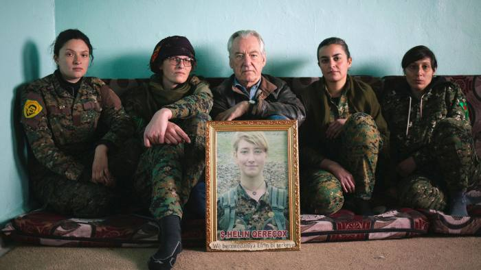 Programme Name: Anna: The Woman Who Went to Fight ISIS - TX: 03/07/2019 - Episode: n/a (No. n/a) - Picture Shows: Dirk Campbell holding a portrait of his daughter Anna, with International YPJ soldiers - (C) BBC - Photographer: Seb Rabas