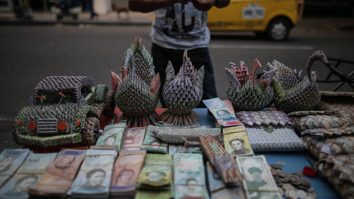 A vendor sells sculptures, made from Venezuelan Bolivar banknotes, near the Simon Bolivar International Bridge in the town of La Parada on the outskirts of Cucuta, Colombia, on Wednesday, Feb. 6, 2019. Venezuela'sNicolas Maduro blames U.S. imposed sanctions for shortages of food and medicine that existed long before, said he will not allow the delivery of humanitarianaidexpected to reach Venezuelan borders as soon as this week.Photographer: Ivan Valencia/Bloomberg