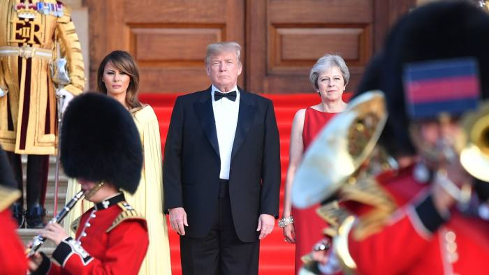 Britain's Prime Minister Theresa May (R) US President Donald Trump (C) and his wife US First Lady Melania Trump (L) stand on steps in the Great Court watching and listening to the bands of the Scots, Irish and Welsh Guards perform a ceremonial welcome as they arrive for a black-tie dinner with business leaders at Blenheim Palace, west of London, on July 12, 2018, on the first day of President Trump's visit to the UK. The four-day trip, which will include talks with Prime Minister Theresa May, tea with Queen Elizabeth II and a private weekend in Scotland, is set to be greeted by a leftist-organised mass protest in London on Friday. / AFP PHOTO / POOL / Ben STANSALLBEN STANSALL/AFP/Getty Images