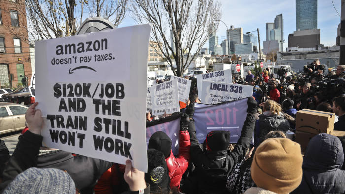 FILE- In this Nov. 14, 2018, file photo protesters carry anti-Amazon posters during a coalition rally and press conference opposing Amazon headquarters getting subsidies to locate in the New York neighborhood of Long Island City, Queens in New York. Amazon said Thursday, Feb. 14, 2019, that it will not be building a new headquarters in New York, a stunning reversal after a yearlong search. (AP Photo/Bebeto Matthews, File)