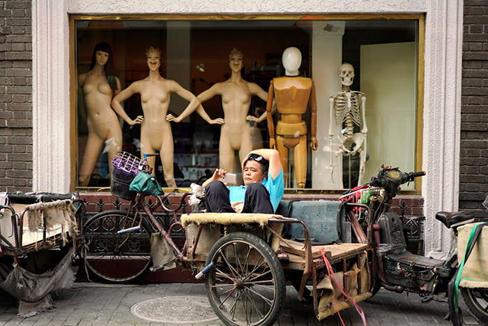 A man looks at his mobile phone on a tricycle outside a mannequin shop in Shanghai, China June 25, 2018. REUTERS/Aly Song